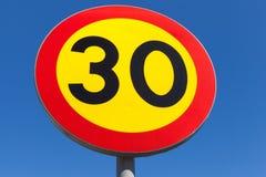 Ljust hastighetsbegränsningvägmärke över blå himmel royaltyfria foton