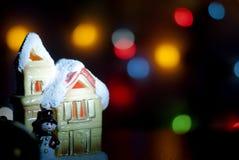 Ljust hus för jul på en bakgrund av färgrik bokeh Arkivbild
