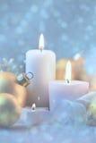 Ljust julpynt med stearinljus, struntsaker och magisk snö arkivfoto