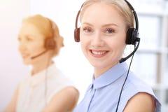 Ljust kontor för appellmitt Två blonda kvinnor i en hörlurar med mikrofon Fotografering för Bildbyråer