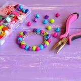 Ljust kulört armband som göras av plast- knappar Handgjorda gulliga ungesmycken Diy barn Royaltyfri Fotografi