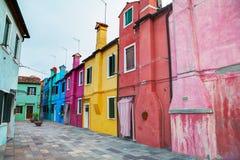 Ljust målade hus på den Burano kanalen Arkivfoto