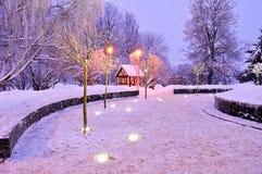 Ljust nattlandskap för vinter med det ensamma huset och fallande snö Arkivbilder