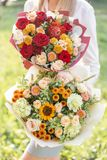 Ljust och delikat, härlig bukett två Ung flicka rymma blommaordningar med variation av färger brigham arkivbild