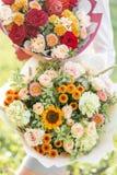 Ljust och delikat, härlig bukett två Ung flicka rymma blommaordningar med variation av färger brigham royaltyfria bilder