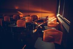 Ljust passerande under gardinen i det tomma klassrumet, orange armstolar Royaltyfri Foto