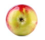 Ljust röd-guling äpple, på en vit bakgrund Saftig, näringsrik, smaklig ljus frukt En healthful frukost royaltyfri fotografi