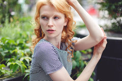 Ljust rödbrun flicka i grön buske på gatan, tonat foto Royaltyfria Foton