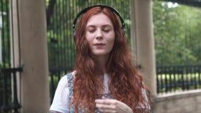 Ljust rödbrun flicka som gör framsidor utomhus- lager videofilmer