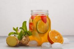 Ljust rödbrun frukt- iste med mintkaramellen i en glass krus, vit bakgrund arkivbilder