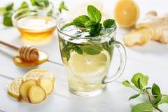 Ljust rödbrun grönt te i ett exponeringsglas för kalla vinterdagar för influensa Sidosikt på vit träbakgrund som dekoreras med mi royaltyfri fotografi