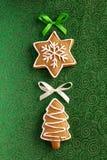 Ljust rödbrun kakor för jul på den gröna bakgrunden Royaltyfria Bilder