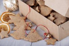 Ljust rödbrun kex i en ask och bredvid en ask en decorat för ` s för nytt år Arkivbilder