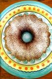 Ljust rödbrun kryddabundtkaka på den färgrika plattan Arkivbild