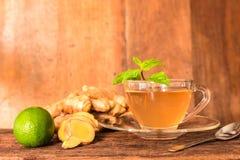 Ljust rödbrun te - kopp av ljust rödbrun te med den gröna citronen royaltyfria bilder