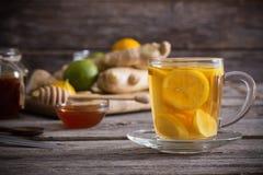 Ljust rödbrun te och ingredienser på grungeträbakgrund Arkivbilder