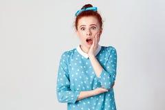 Ljust rödbrun ung flicka som skriker med chock som rymmer händer på hennes kinder Isolerat studioskott på grå bakgrund royaltyfri bild