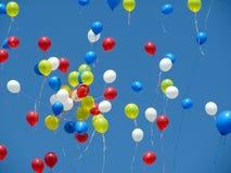 Ljust rött, gulnar, slösar, och vitballonger som är utsläppta in i en blå himmel Royaltyfri Bild