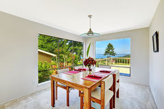 Ljust rum med att äta middag fastställd och härlig fönstersikt för tabell Arkivbild
