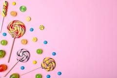 Ljust smaskigt godisar och utrymme för text på färgbakgrund arkivfoto