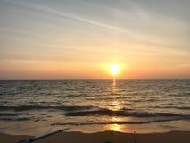 Ljust solnedgångljus att reflektera på den havsyttersida och stranden royaltyfri bild