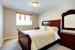 Ljust sovrum med körsbärsrött wood möblemang Arkivfoton