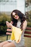 Ljust stilfullt flickasammanträde på en bänk och tabilder av henne Utmärkt ljus makeup, röda pösiga kanter, länge Arkivfoton