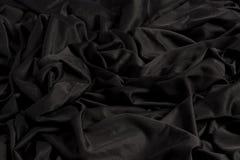 Ljust svart tyg med krusningar och textur med hårt ljus och mörkt ljus royaltyfria foton