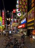 Ljust tänd gata med talrika affischtavlor och neon i Dotomb Arkivfoto