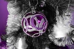 Ljust upplyst julgran med purpurfärgad garnering på en purpurfärgad bakgrund arkivbilder