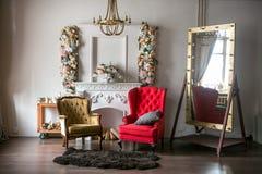 Ljust vind-stil rum med en röd fåtölj, en brun fåtölj, en vit spis med blommor, en stor spegel med ljusa kulor och fotografering för bildbyråer