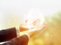 Läka cirkeln av ljus, öppnar den gamla kvinnliga botemedelen med händer upp omgivet av en vit cirkel av färg- och vitstjärnaljus Arkivfoto