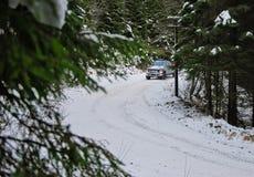 LKW 4x4, der auf Winterschneestraße im Wald treibt Lizenzfreie Stockbilder