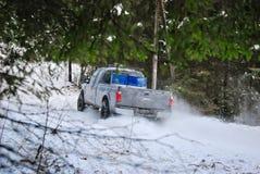 LKW 4x4, der auf Winterschneestraße im Wald treibt Lizenzfreie Stockfotografie