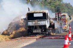 LKW, der das Heu demoliert durch Feuer schleppt. lizenzfreies stockbild