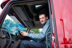 LKW-Fahrer halb im LKW-Fahrerhaus mit modernem Armaturenbrett Lizenzfreies Stockfoto