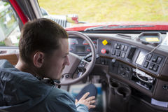 LKW-Fahrer halb im LKW-Fahrerhaus mit modernem Armaturenbrett Lizenzfreie Stockfotografie