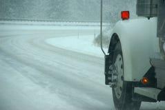 LKW-Gummireifen, die auf Datenbahn während des Schneesturmes spinnen stockbild