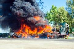 LKW im Feuer mit schwarzem Rauche auf der Straße Lizenzfreie Stockbilder