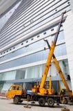 LKW-Kräne vor modernem Gebäude Lizenzfreie Stockfotografie