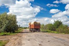 LKW mit Ballen Heu fährt auf die Straße Lizenzfreies Stockbild