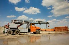 LKW mit dem Kran, der an der Baustelle arbeitet Lizenzfreie Stockfotos
