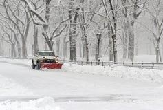 LKW mit Schneepflugreinigungsstraße während des Schneesturmes Stockfoto
