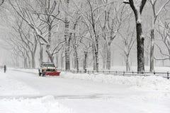 LKW mit Schneepflugreinigungsstraße während des Schneesturmes Lizenzfreies Stockfoto
