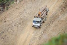 LKW transportiert anmeldet einen Schotterweg stockfoto