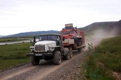 LKW transportiert aufgespürtes Geländefahrzeug an der Schotterstraßetundra Lizenzfreie Stockbilder