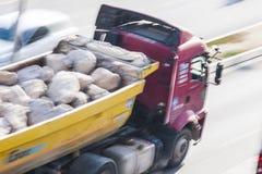 LKW voll von Felsen läuft auf der Straße Lizenzfreie Stockfotos