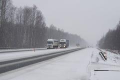 LKWs auf der Autobahn in einem Blizzard Lizenzfreies Stockfoto