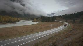 LKWs, die auf eine kurvenreiche Straße entlang Fluss an einem regnerischen Tag des bewölkten Herbstes, Sibirien, Altai reisen stock footage