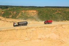 LKWs gehen unten in eine Grube hinter Sand Stockbild